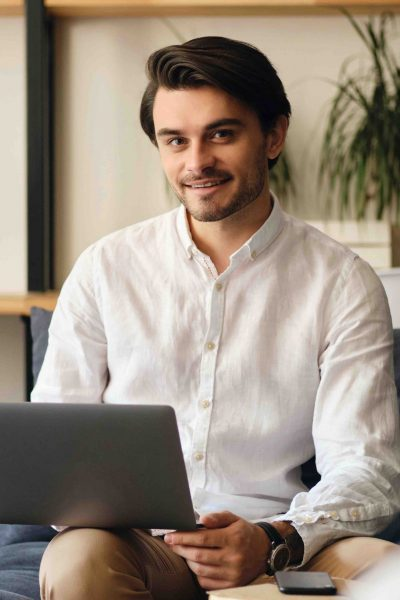 Young attractive smiling businessman sitting on sofa with laptop happily looking in camera in modern co-working space